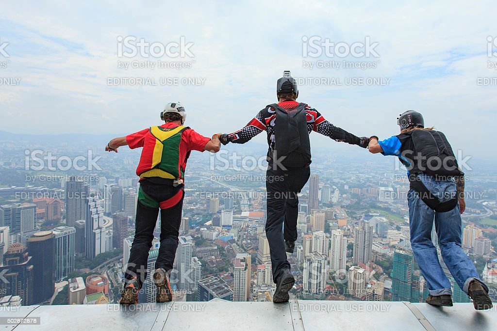 BASE jumpers in jumps off from Kuala Lumpur Tower, Malaysia. stock photo