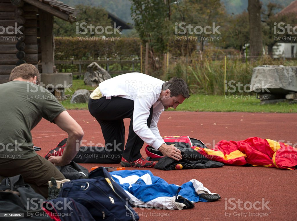 BASE jumpers prepare parachutes before making jump stock photo