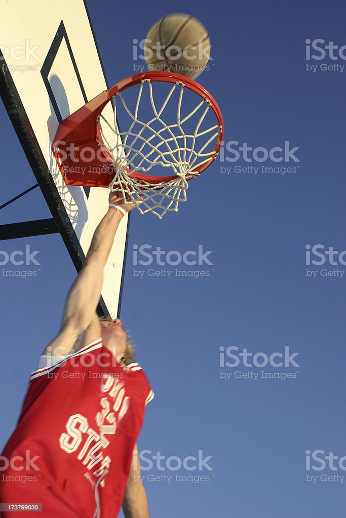 Jumping basketball player makes shot in an outdoor court royalty-free stock photo