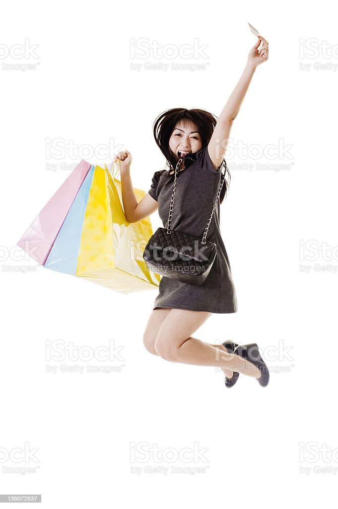 Jumping Chinese woman holding shopping bags and credit card. royalty-free stock photo