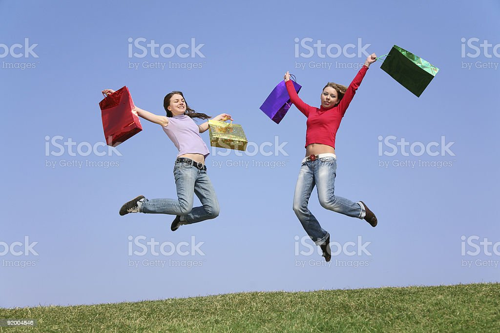 jumping couple girls with bags 2 royalty-free stock photo