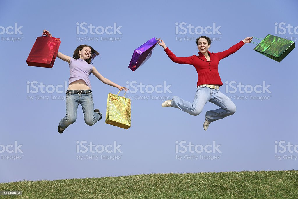 jumping couple girls with bags royalty-free stock photo