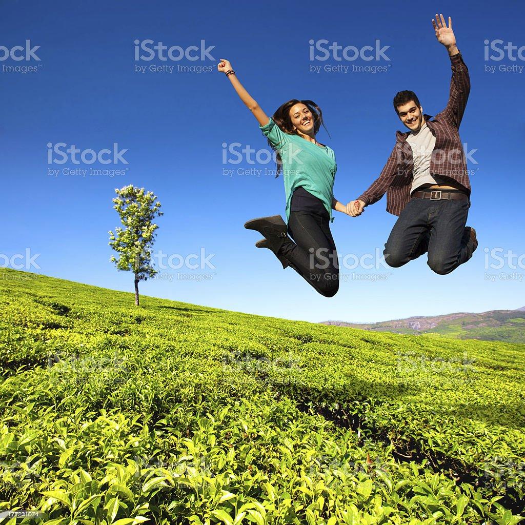 Saut de couple dans le champ vert. photo libre de droits