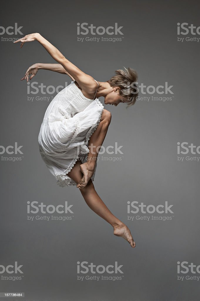 Jumping female dancer wearing a white dress stock photo