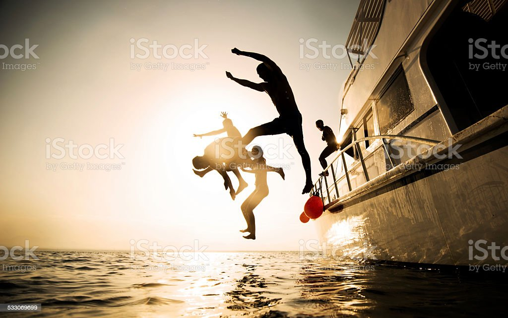 Jumping from the boat at sunset. stock photo