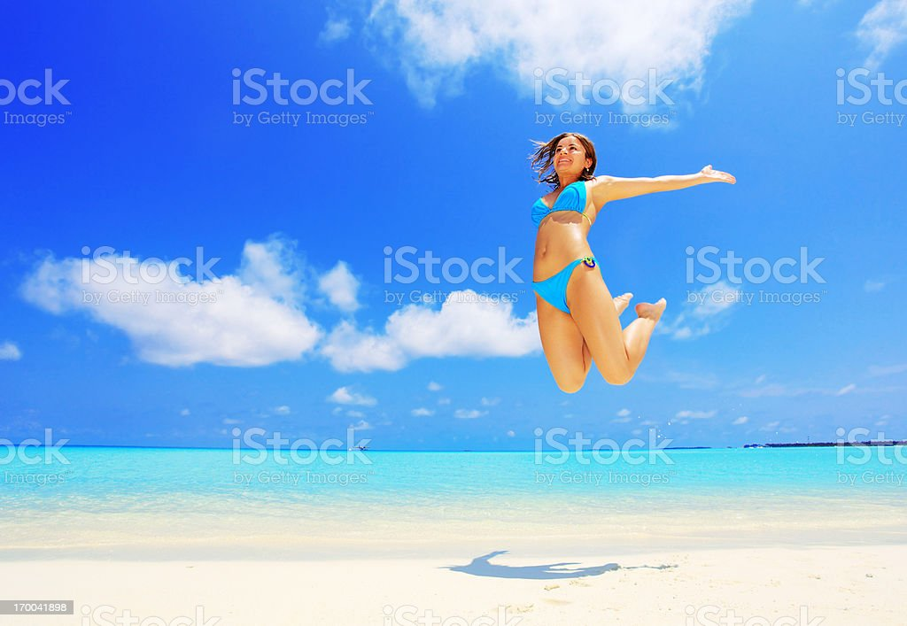 Jumping girl on white sand beach against azure sea. royalty-free stock photo
