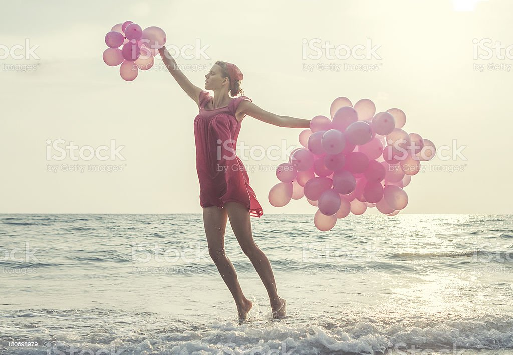 jumping girl with pink balloons stock photo