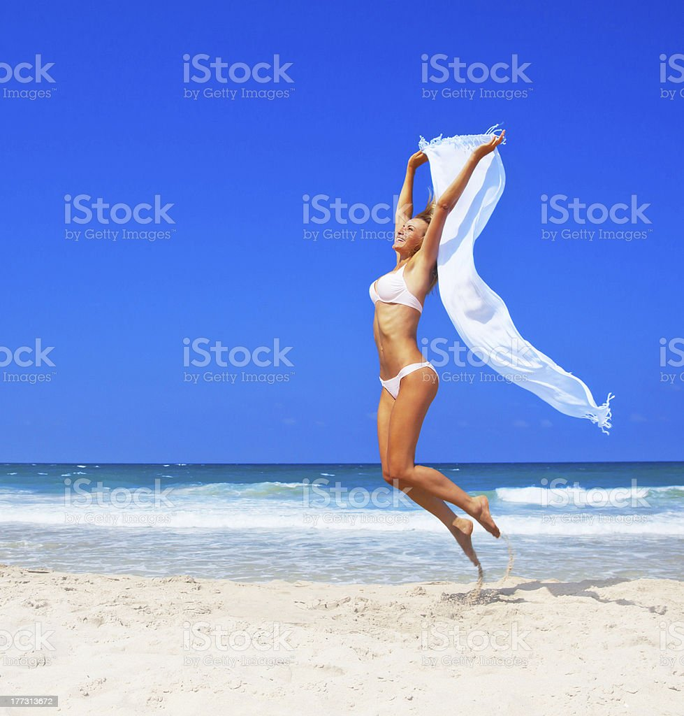 Jumping happy girl on the beach royalty-free stock photo