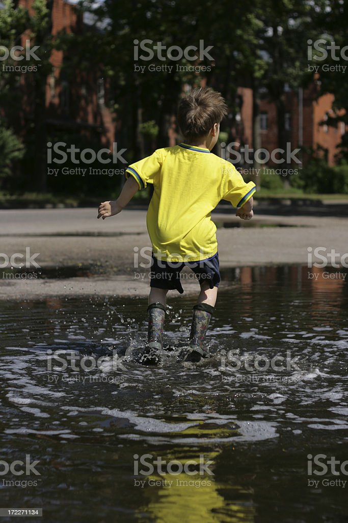 Jumping in muddy puddle royalty-free stock photo