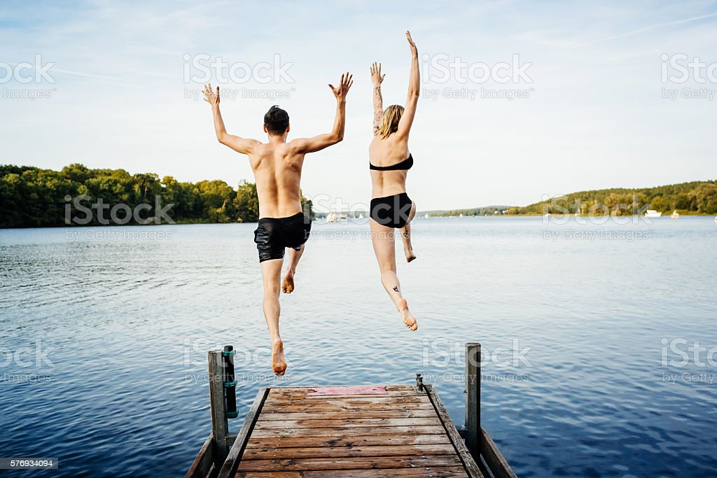 Jumping into the water from a jetty stock photo