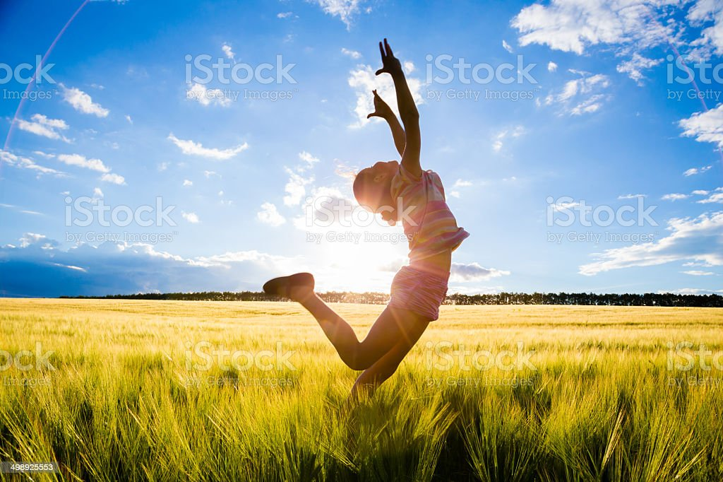jumping kid on the field stock photo