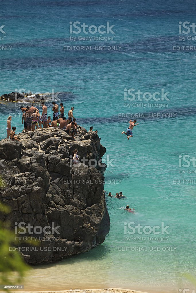 Jumping off rock on Oahu, Hawaii stock photo