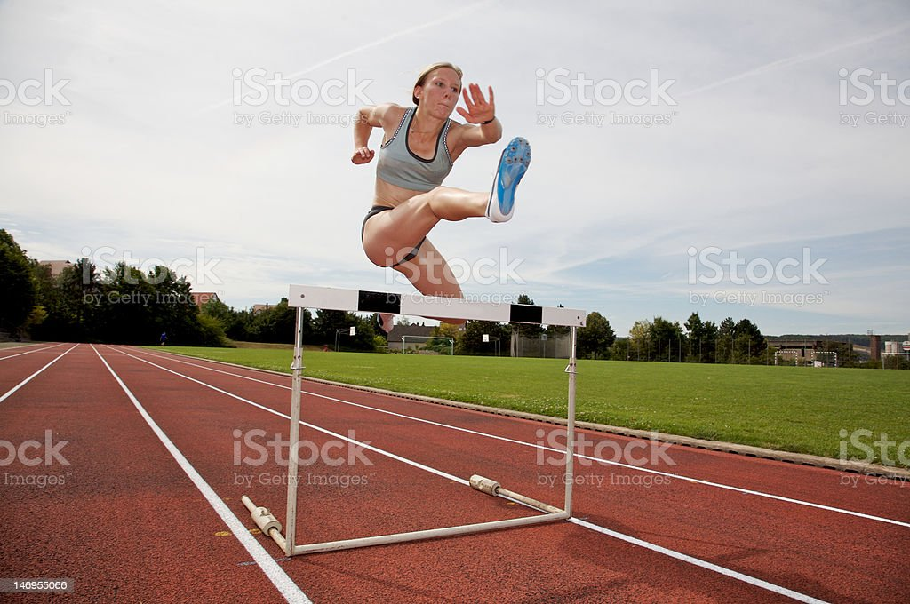 Jumping over a hurdle stock photo
