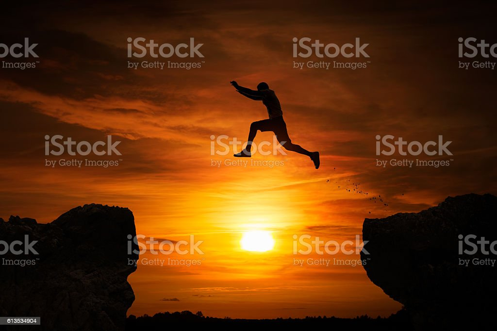 Jumping over abyss stock photo