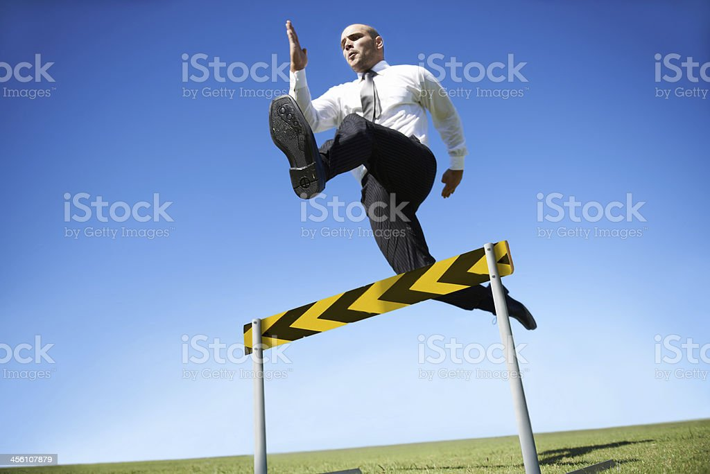Jumping over business hurdles stock photo
