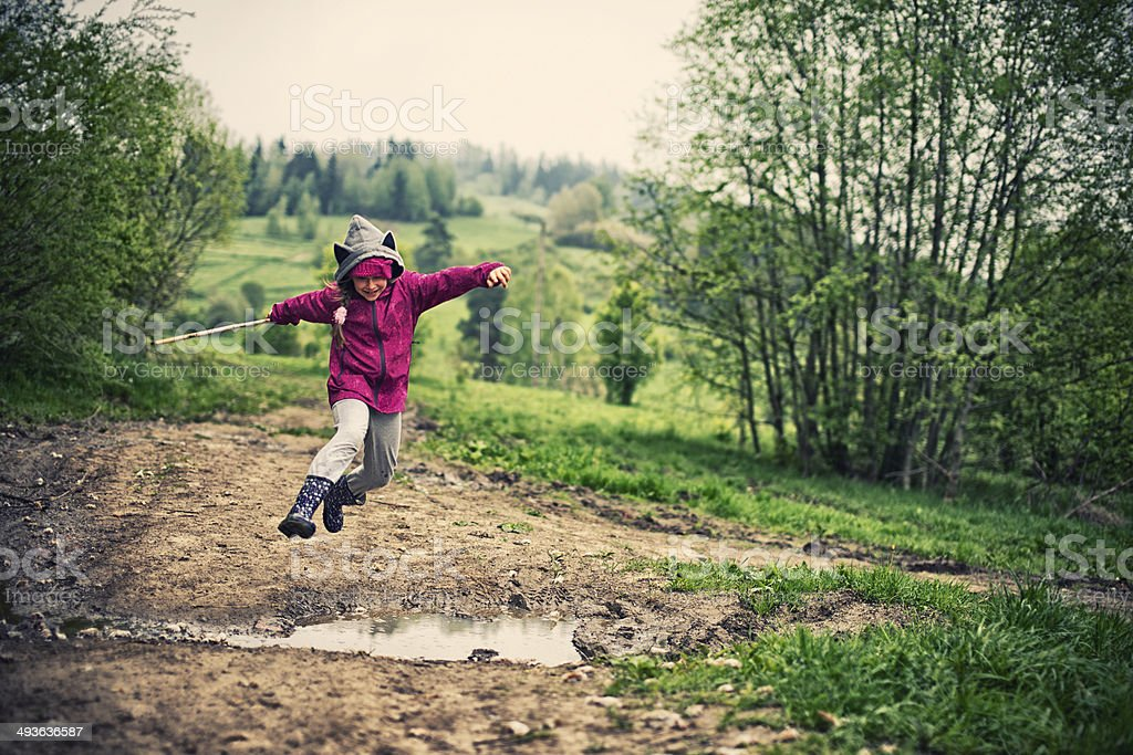 Jumping over spring puddles stock photo