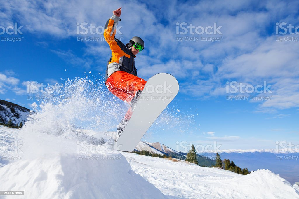 Jumping snowboarder from hill in winter stock photo