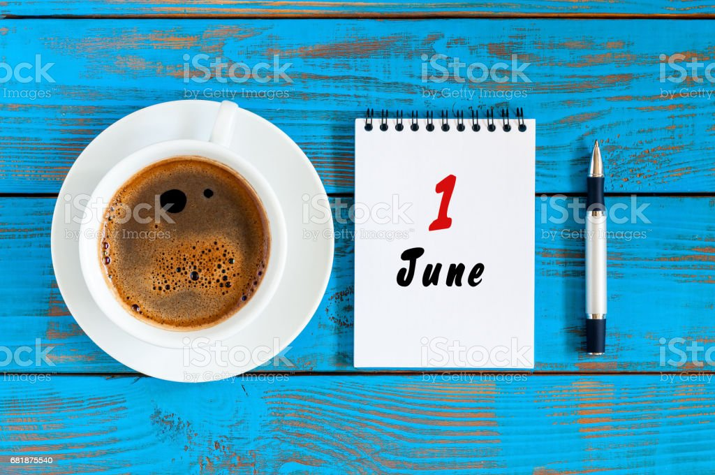 June 1st. Day of the month 1 , everyday calendar with morning coffee cup at blue wooden background. Summer concept, Top view stock photo