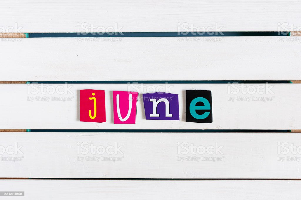 June written with color magazine letter clippings on white wooden stock photo
