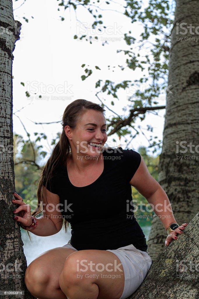 Junge Frau sitzt auf einem Baum stock photo