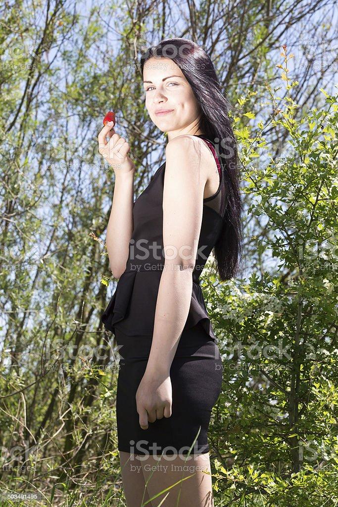 Junge huebsche Frau mit Erdbeere in Natur stock photo