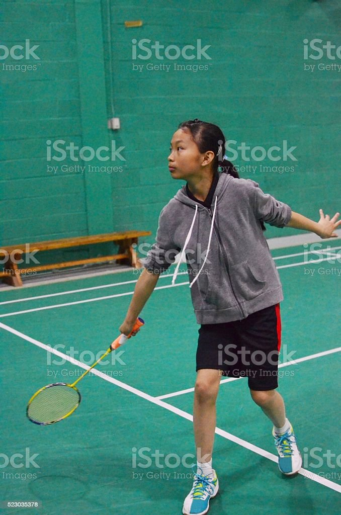 Junior badminton player playing on the court stock photo