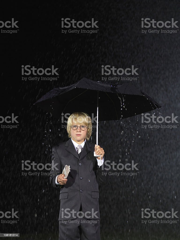 Junior businessman holding an umbrella royalty-free stock photo