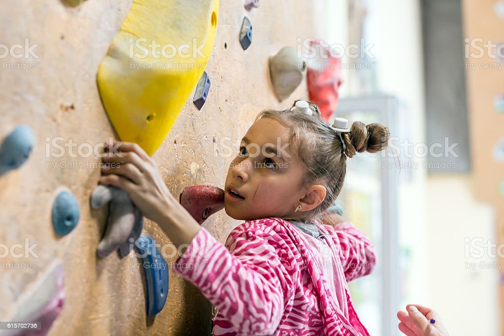 Junior Climber hanging on holds on climbing wall stock photo