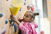 Junior Climber hanging on holds on climbing wall