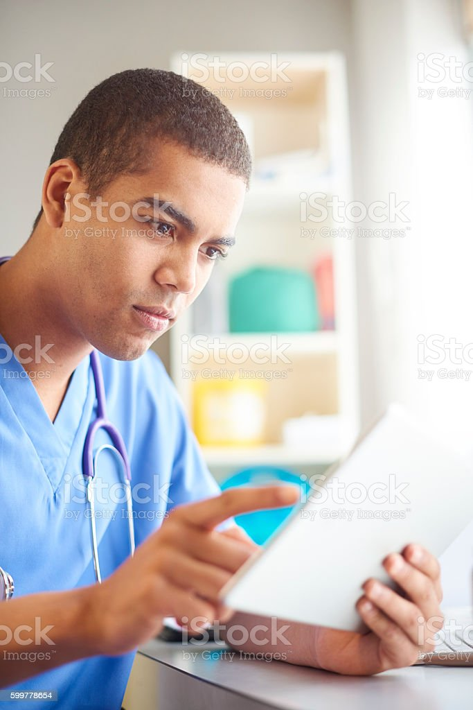 junior doctor looking through medical notes stock photo