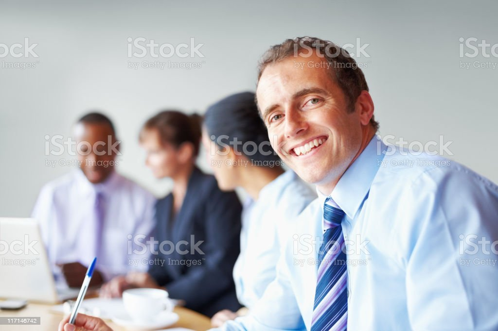 Junior executive at meeting, with team in background royalty-free stock photo