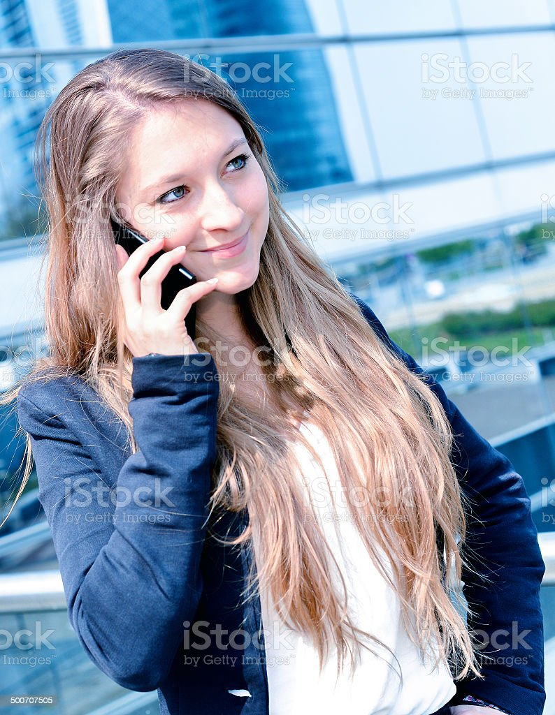 Junior executive dynamic phoning outside of her office royalty-free stock photo