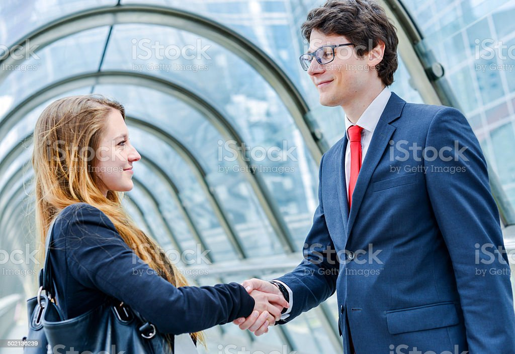 Junior executives dynamics shaking hands royalty-free stock photo