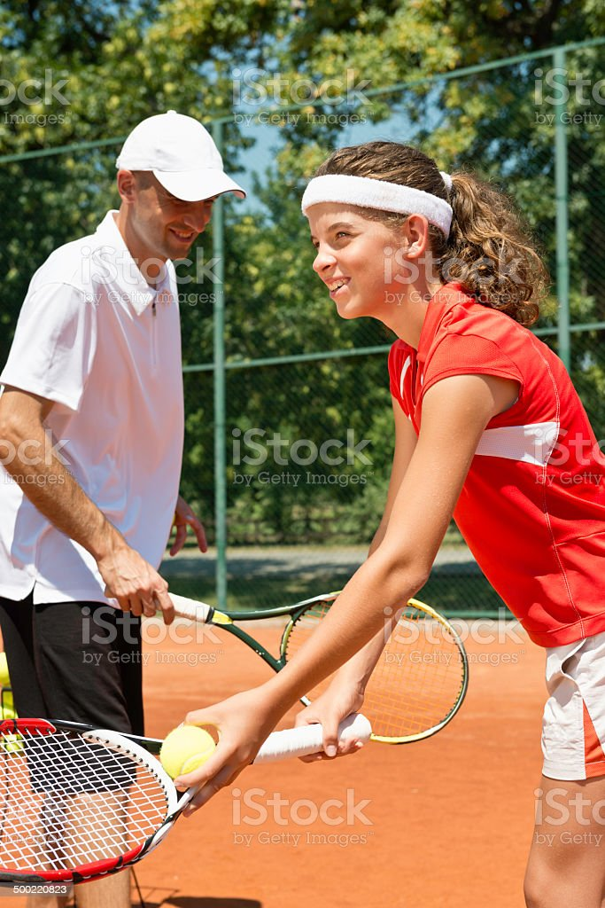 Junior female tennis player with coach royalty-free stock photo