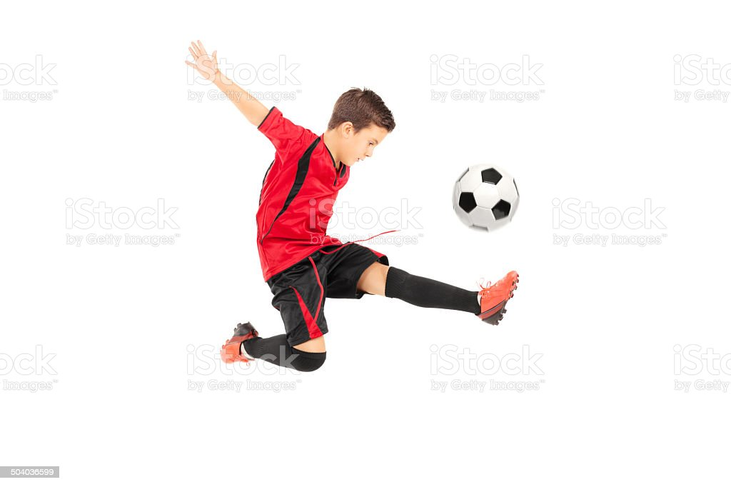 Junior football player kicking a ball stock photo