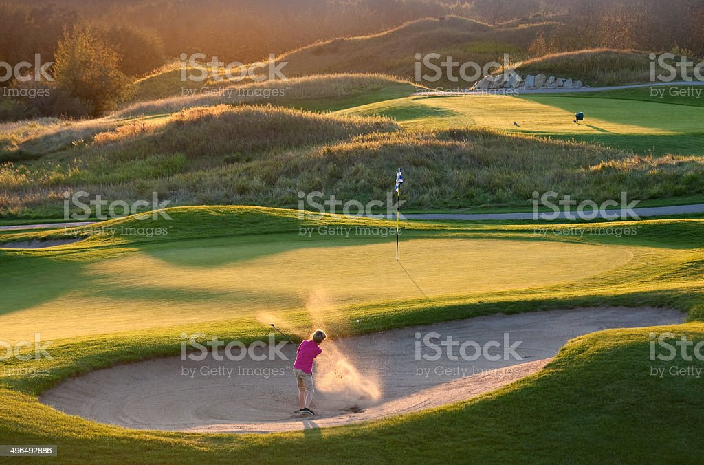 Junior Golfer Hitting Bunker Shot on Beautiful Golf Course stock photo
