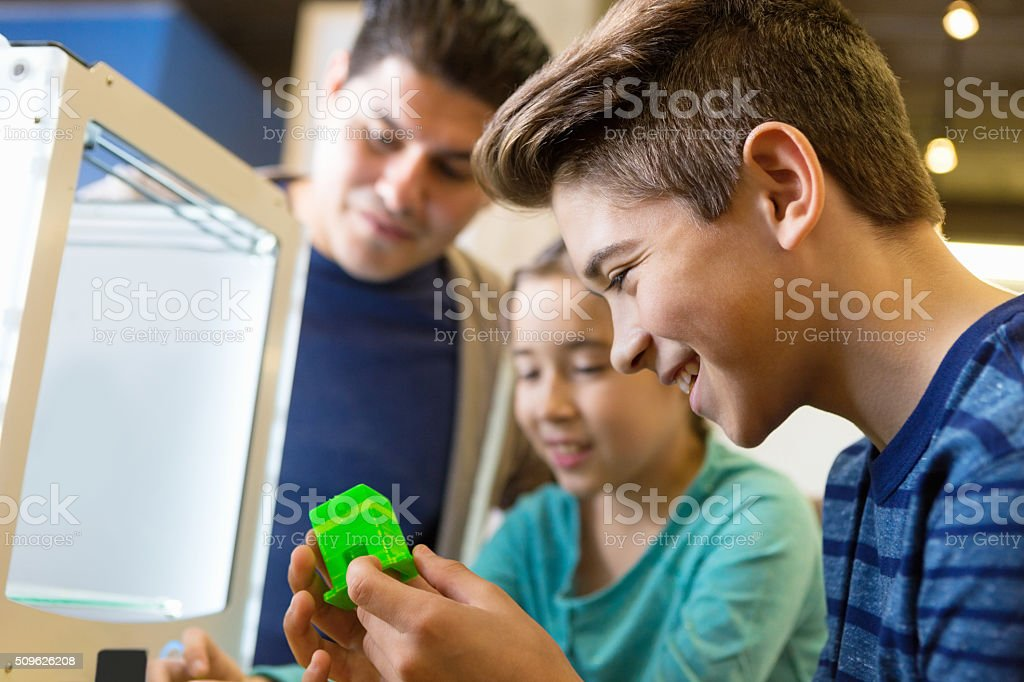 Junior high school student using 3D printer with family stock photo