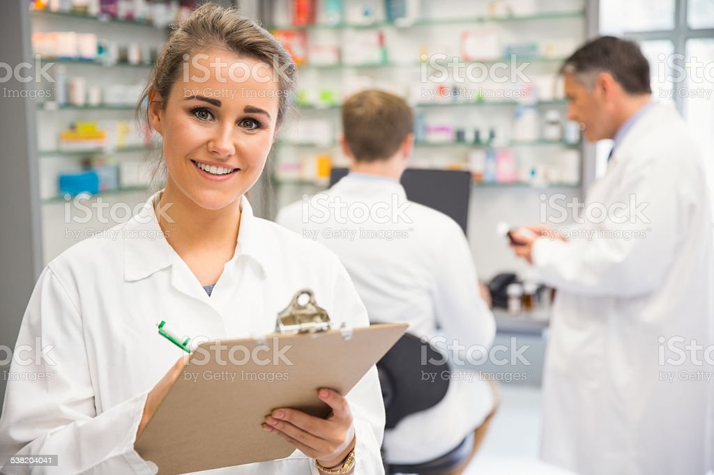 Junior pharmacist writing on clipboard stock photo