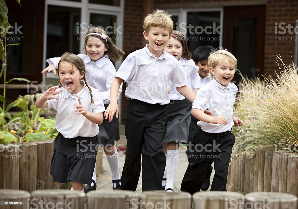junior school: children smiling and running in school uniforms royalty-free stock photo