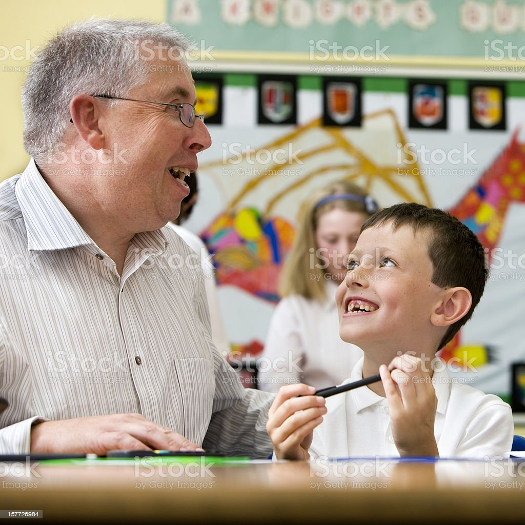 junior school: teacher and pupil working together royalty-free stock photo