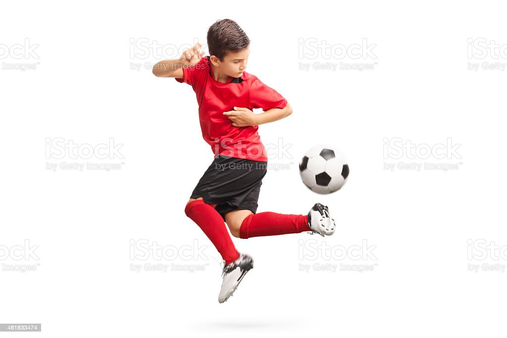 Junior soccer player performing a trick stock photo