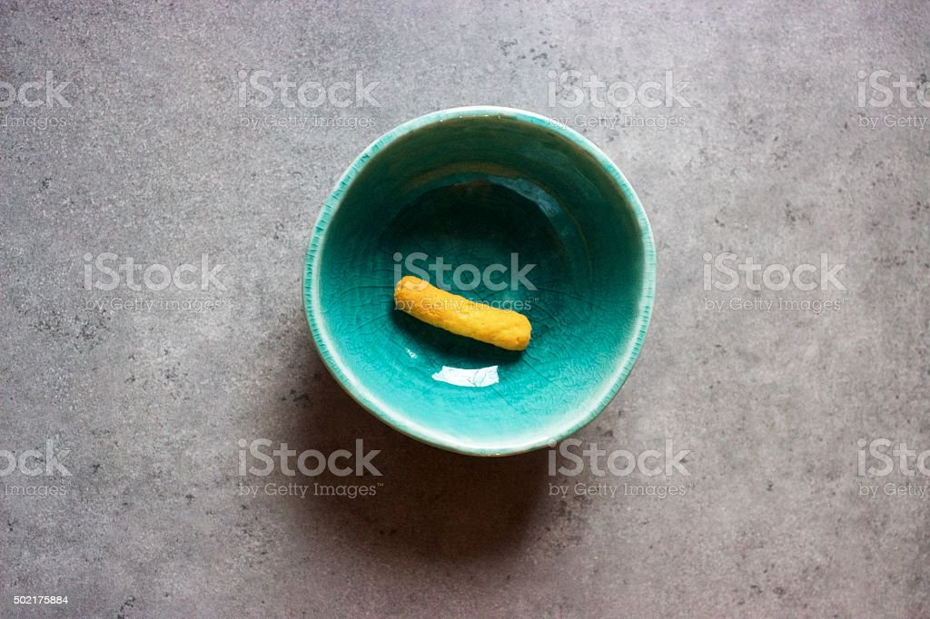 Junk food: single cheese puff in green bowl in kitchen stock photo