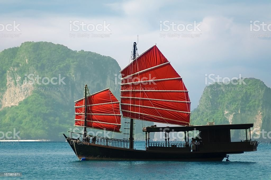 Junk ship with mountain island background stock photo