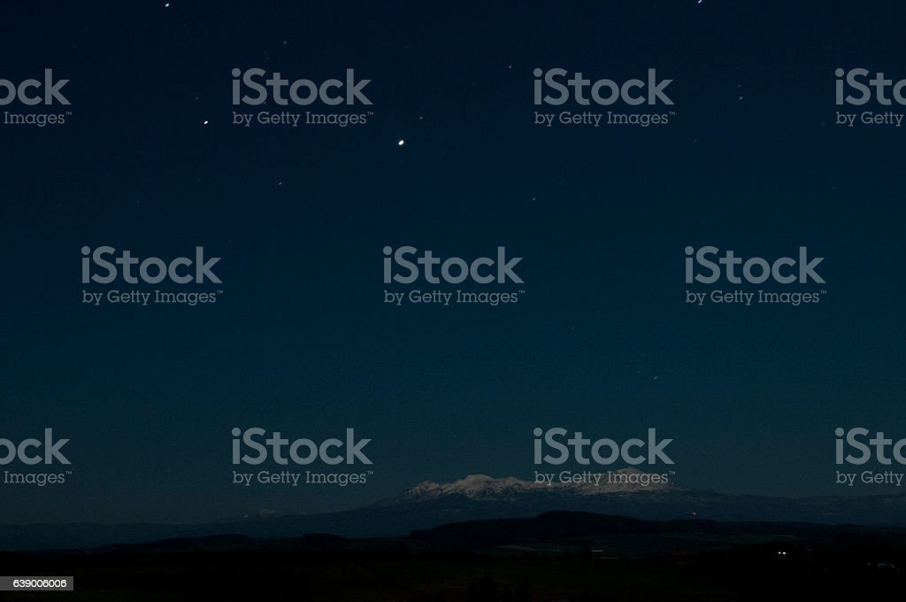 Jupiter and snowcapped mountain stock photo