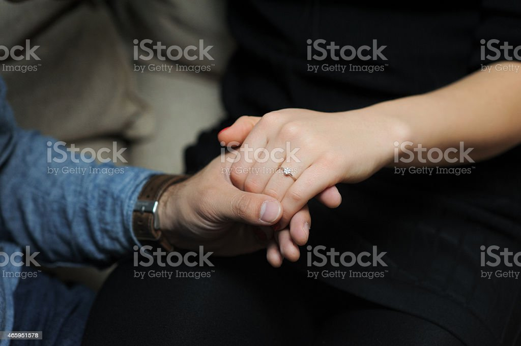 just engaged couple holding hands at restaurant stock photo