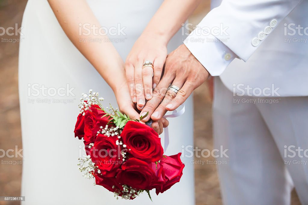 Just married couple compare their wedding rings with a bouquet. stock photo