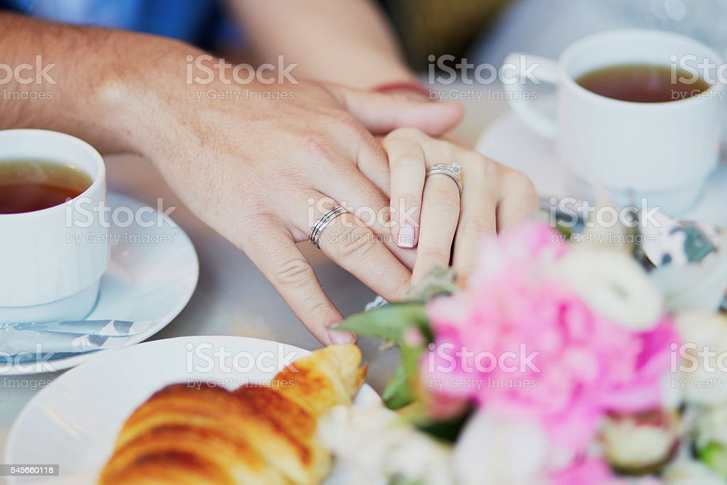 Just married couple holding hands in Parisian cafe stock photo