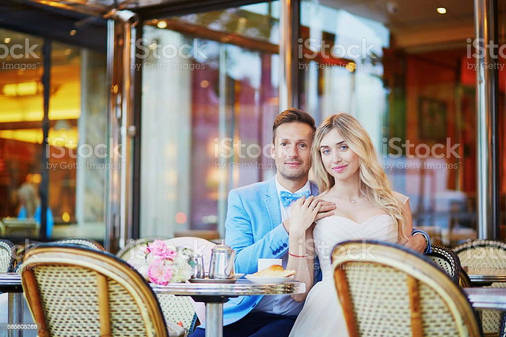 Just married couple in traditional Parisian cafe stock photo