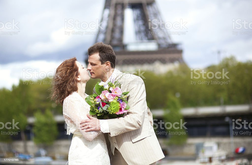 Just married couple is kissing near the Eiffel Tower royalty-free stock photo