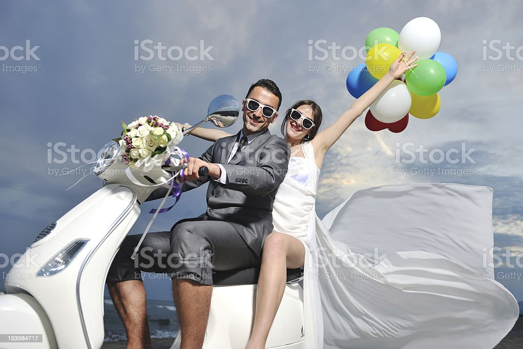 Just married couple ride a white scooter royalty-free stock photo